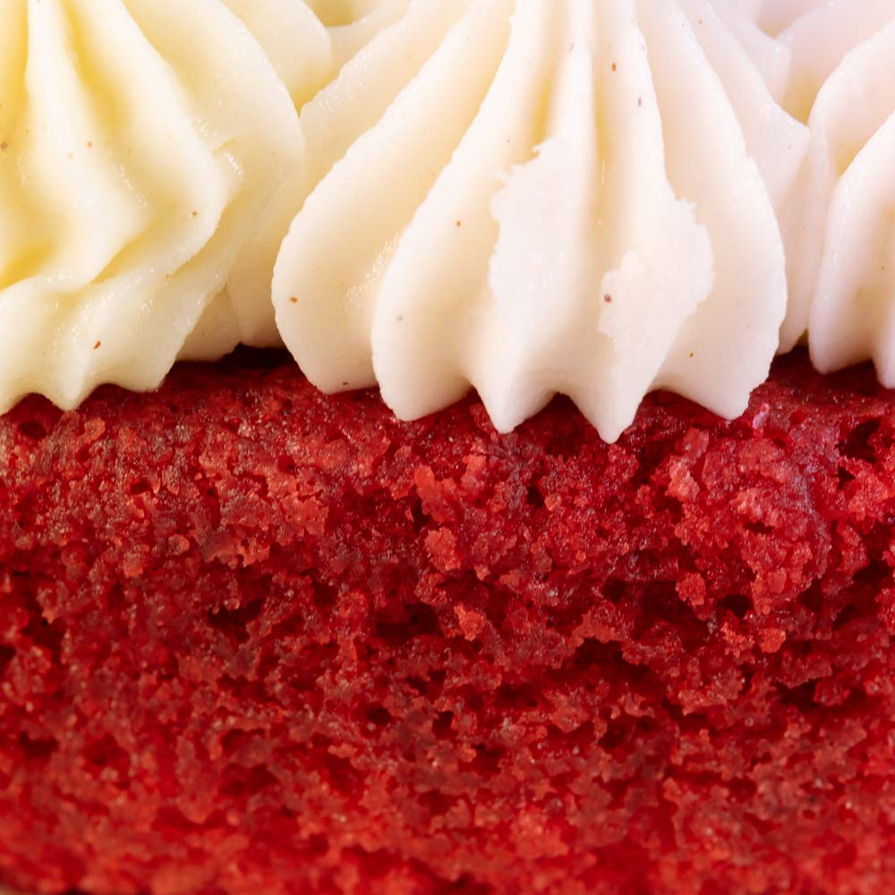 Close up of the butter cream frosting on a red velvet cake