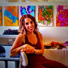 Elysa smiling in her studio with marbled paintings