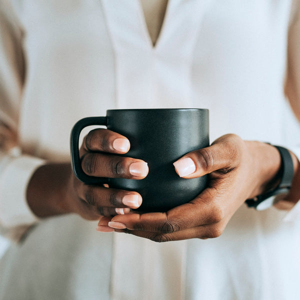women holding a cup of tea. tea time before bed helps promote better sleep