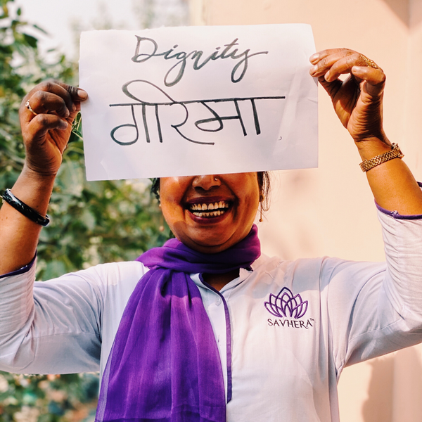 Empowered Women holding up a Dignity sign. Savhera essential oils