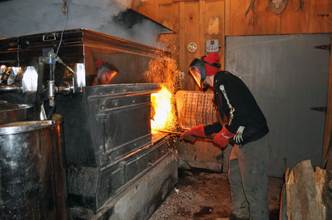 Working the evaporator to make maple syrup