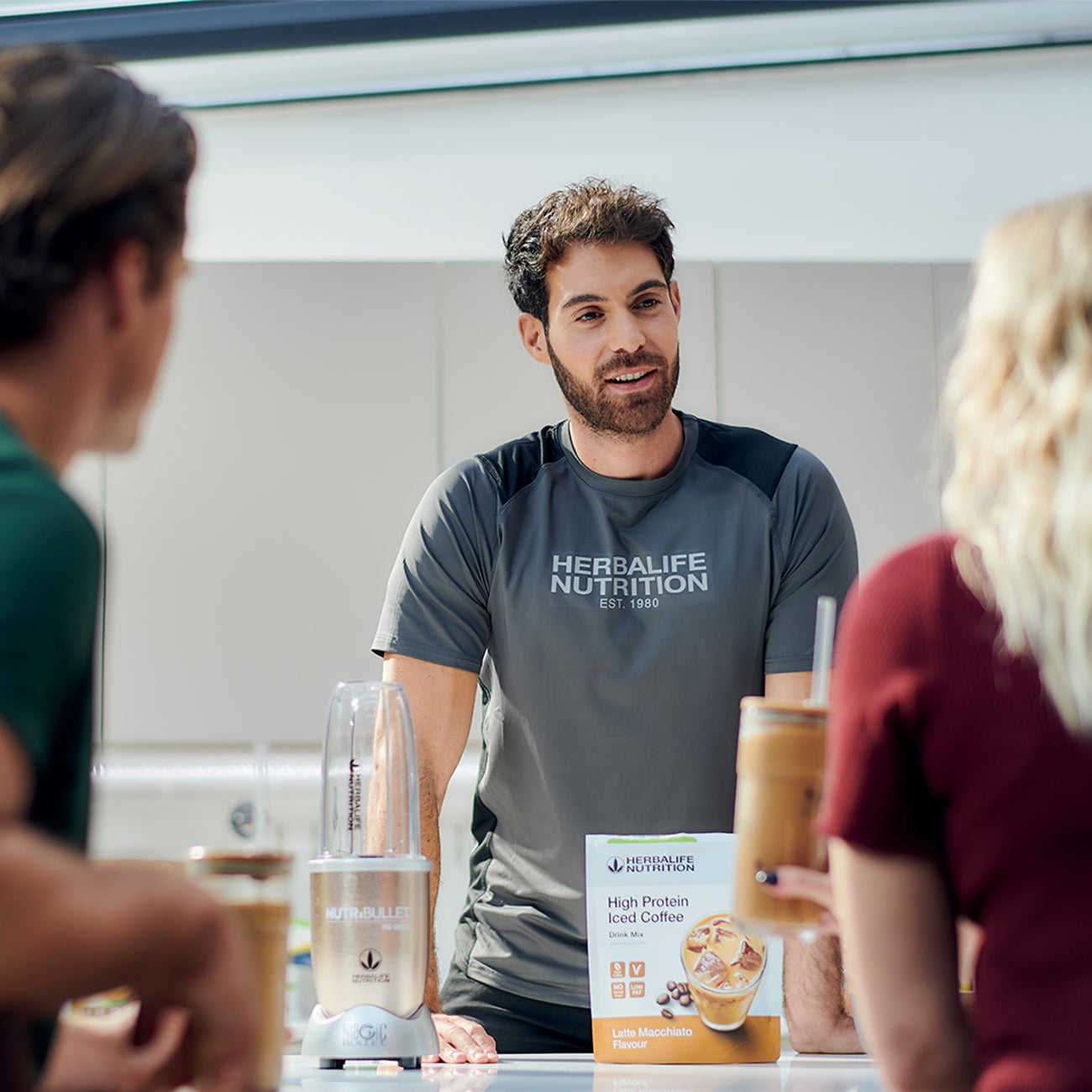 herbalife nutrition coach talking to his customers in a nutrition club