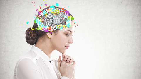 Female with hands clasped under chin, looking down, and thinking. Color brain mechanism graphic.