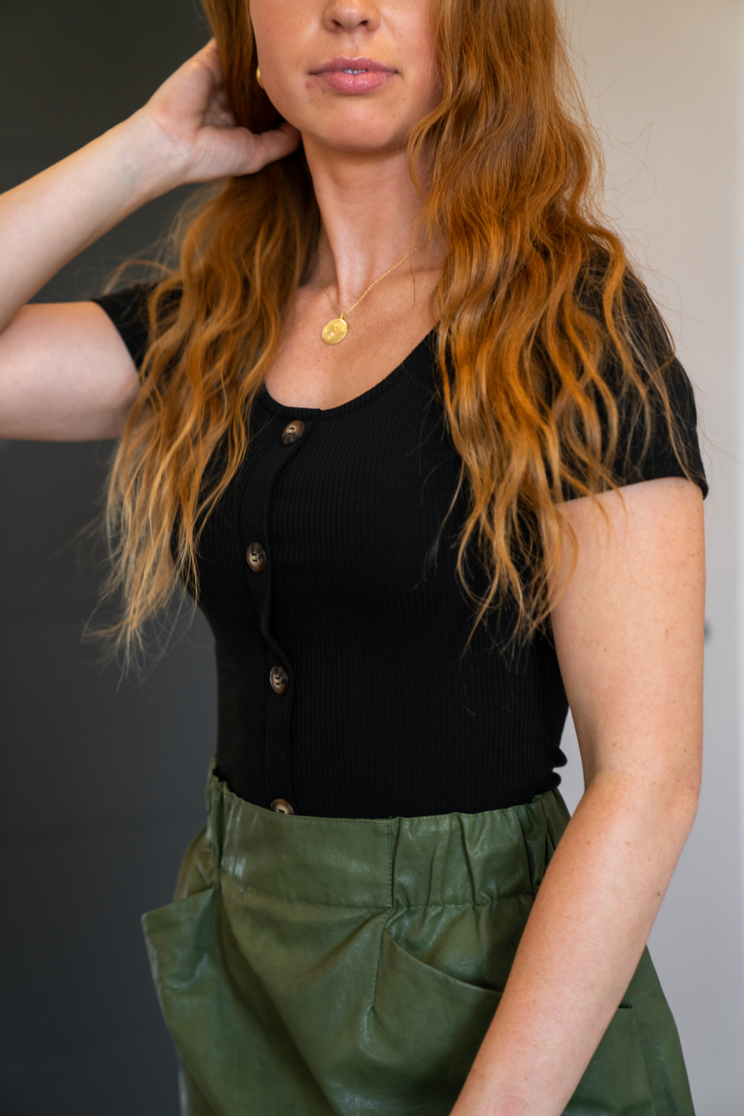 The Short Sleeve Bodysuit that goes with everything. Wooden faux buttons that gives it the perfect touch. Wooden buttons are the thing right now, and this ribbed bodysuit has it all. A favorite she will be, in your closet.
