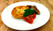 Zucchini & goats cheese quiche with creamed spinach & tomato & pork chipolata