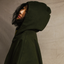 Side view of woman looking into the distance wearing the hood on a Mónica Cordera poncho in green.