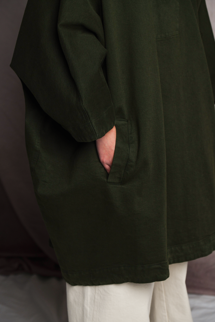 Lower half of person wearing Mónica Cordera poncho in green with their hands in front pockets.