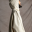 Side view of female standing wearing the hood on the Mónica Cordera poncho in color natural.