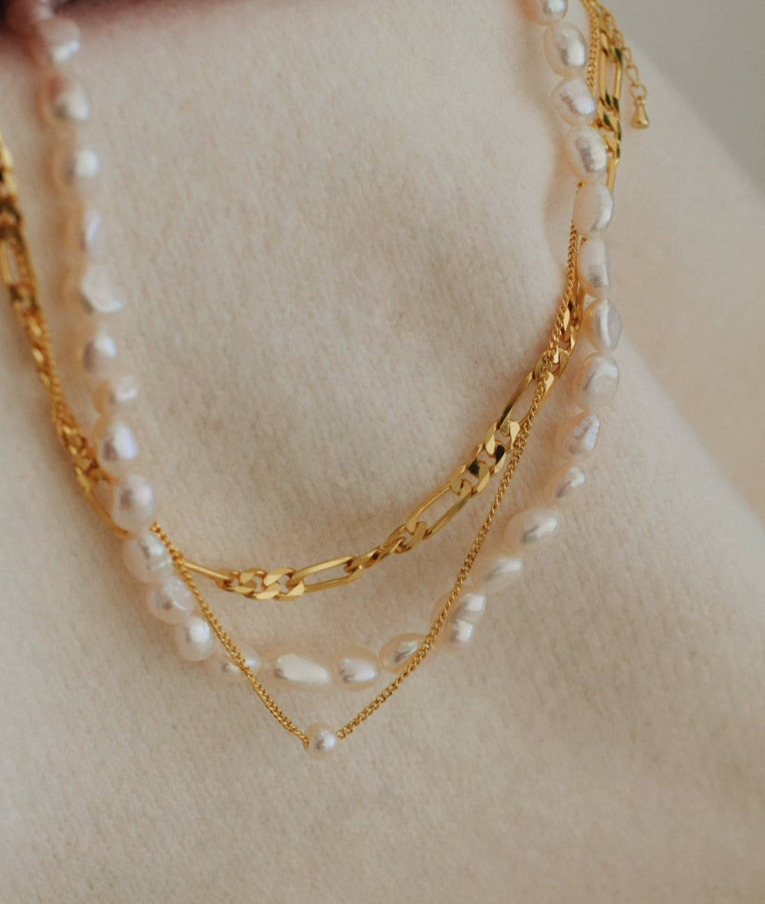 classic white pearl necklace paired with a 18 kt gold figaro chain necklace and a single pearl necklace. All the pieces are layered at 18 kt gold plated on sterling silver available in Kuwait