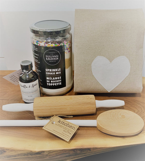 Cookie mix, linen towel, vanilla extract, mixing spoon and rolling pin.