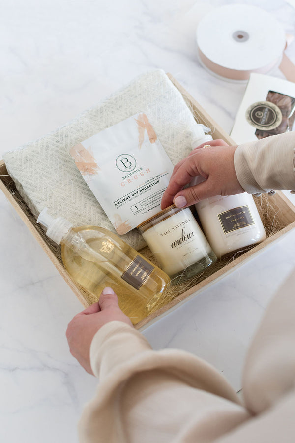 A gift featuring a cashmere scarf, body wash and lotion, candle, chocolates and bath soak.