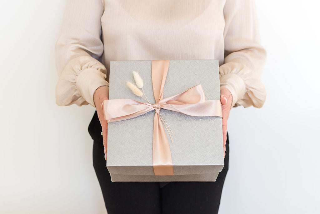 Woman holding a silver gift box with pink ribbon