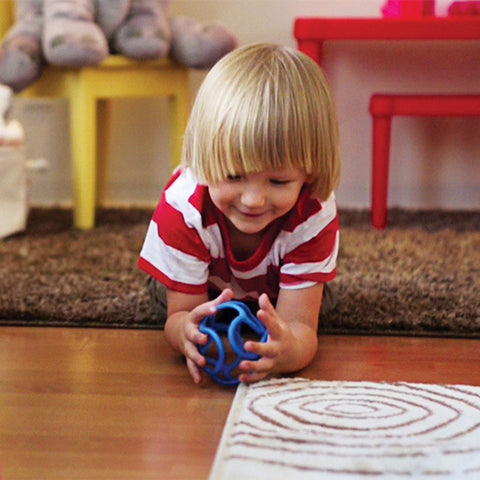 child lying on the floor playing with an OgoBolli ball