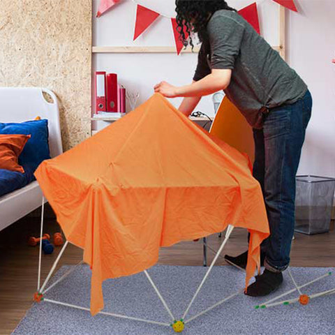 a woman constructs a tent structure in a bedroom using an OgoBILD POD set