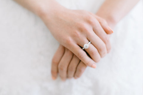 close up of brides clasped hands with diamond engagement ring on finger