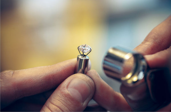 close up of jeweller hands holding a loupe inspecting a diamond from the side