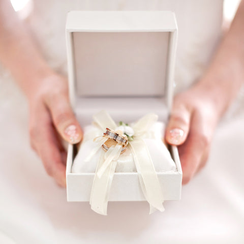 Close up of bride holding a jewellery box with a bow tying two wedding bands together