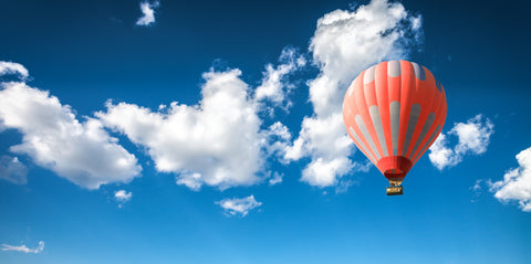 orange hot air ballon in the sky with clouds
