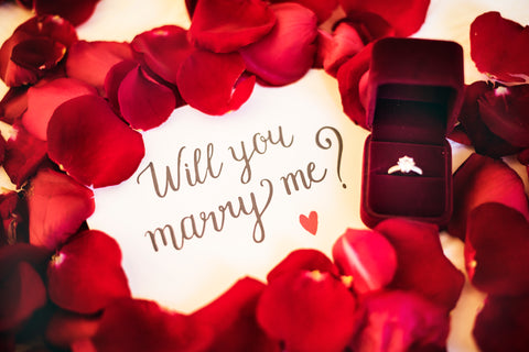 Jewellery box with ring in it and rose petals surrounding the words 'will you marry me?'
