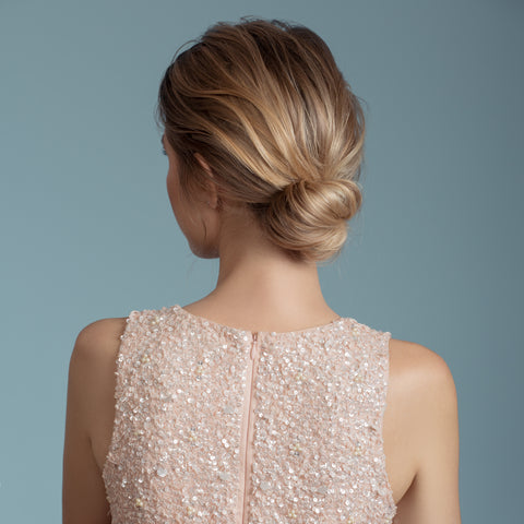 Bride with bun hairdo back facing camera in a soft pink bead dress