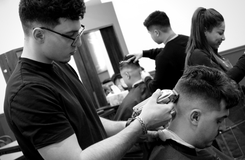 barber student fading hair with model