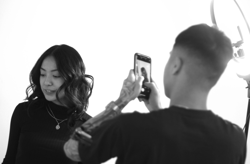 Hair school student taking picture of happy salon client