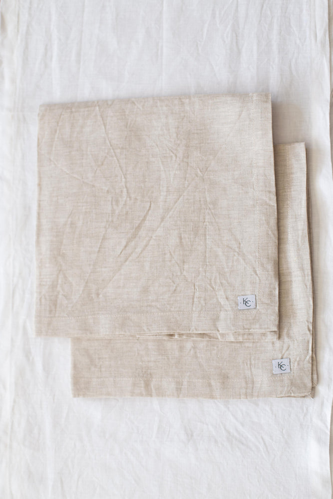 A set of four 100% linen dinner napkins in neutral tones.