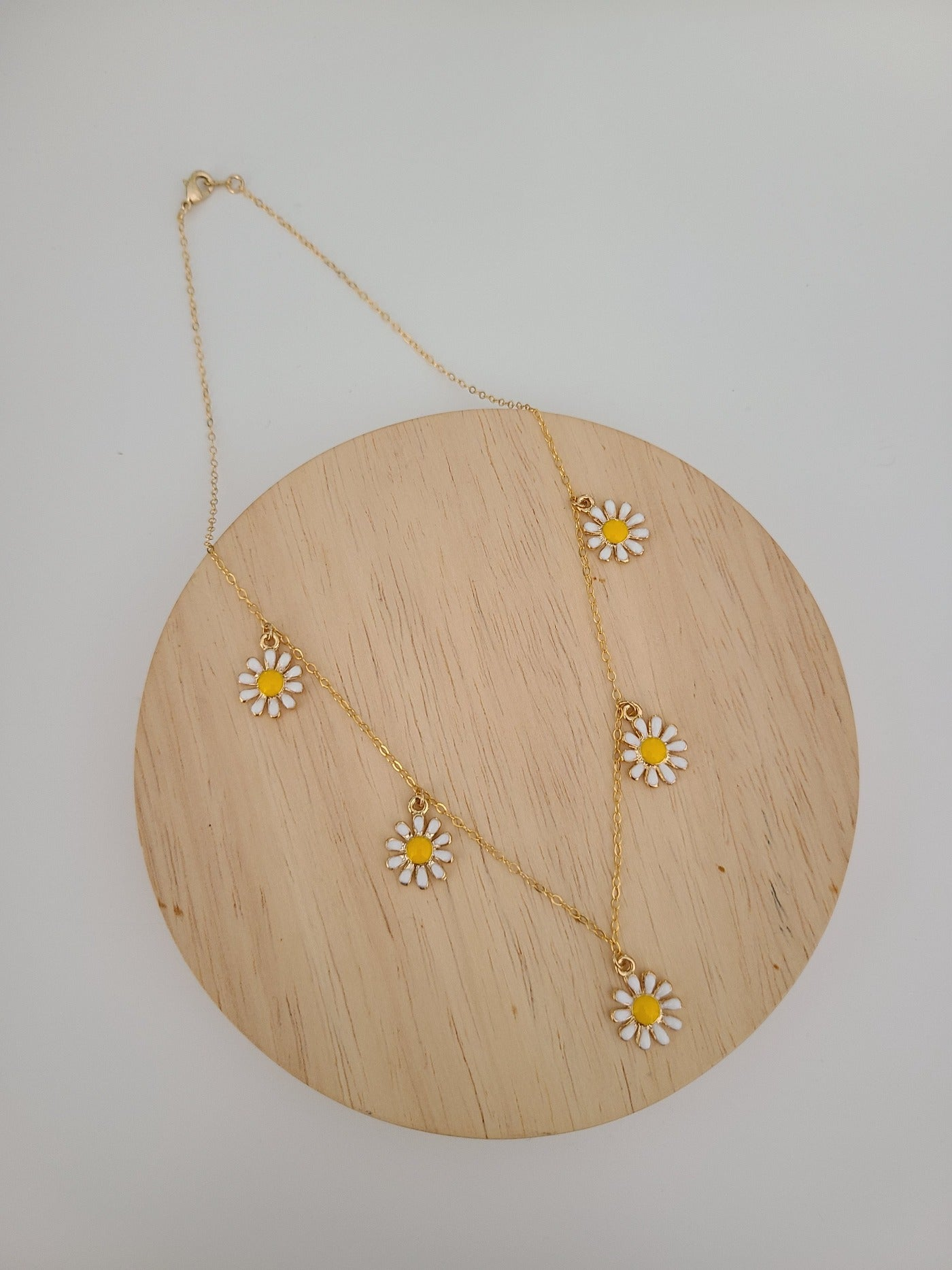 The Hanna Mae Necklace features five daisy charms on a 16 inch gold vermeil chain with a lobster clasp. Retro and cool!