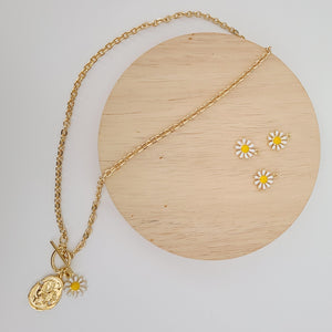 The Traveling Daisy Necklace features a thicker flat rolo chain which is brass base with 18k fill. It has a toggle clasp with white epoxy daisy and an asymmetrical textured coin pendant.