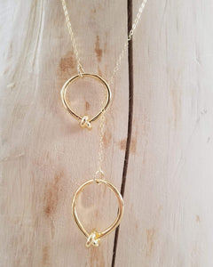 "Long delicate gold lariat necklace with two gold knot rings. Chain is 26"" long gold vermeil. The perfect piece to throw over T's and sweaters.  Versatile,  easy,  funky, minimal design,  light weight."