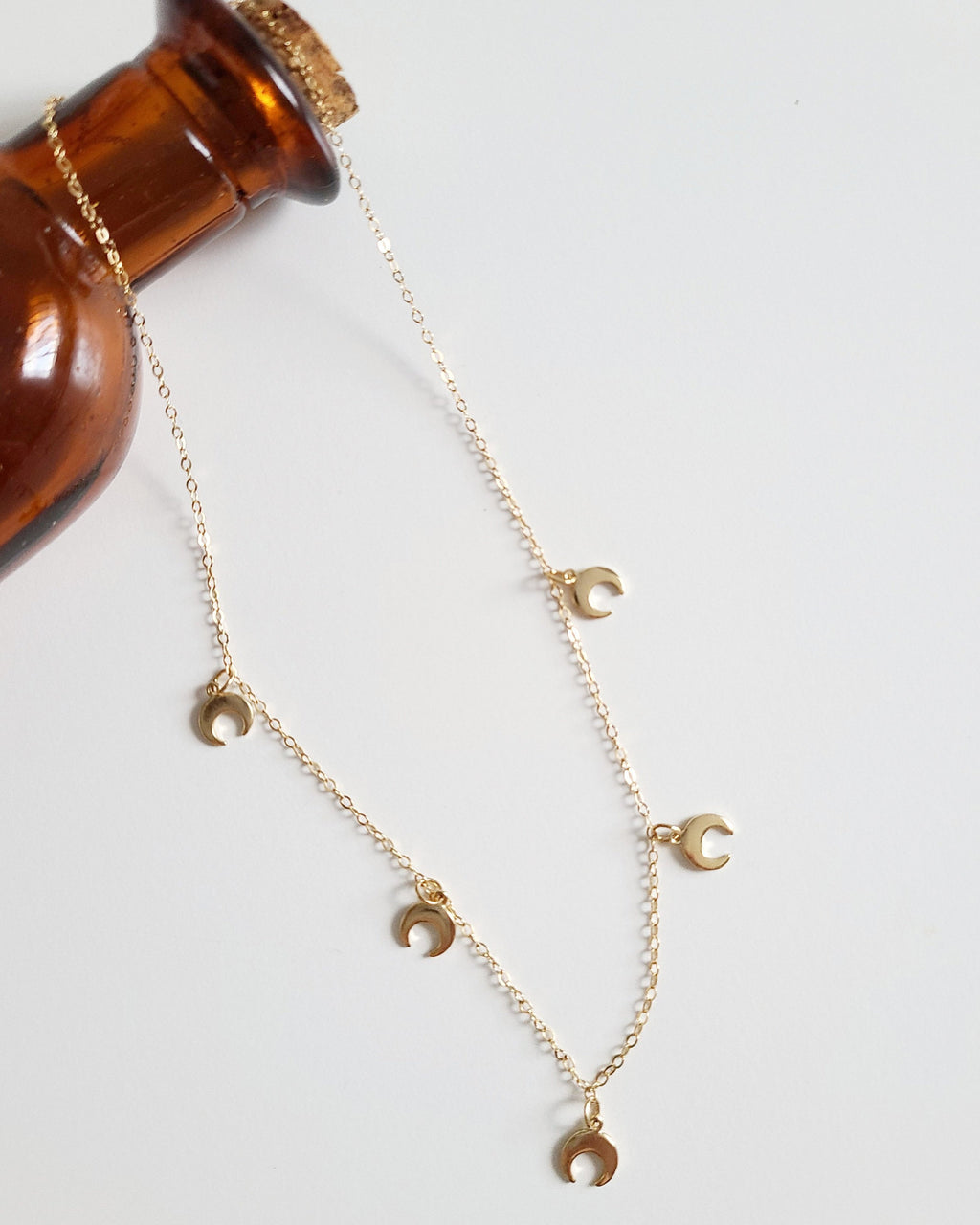 "The Luna Necklace is a 16"" gold vermeil charm necklace. It features 5 crescent moon charms and a dainty lobster clasp."
