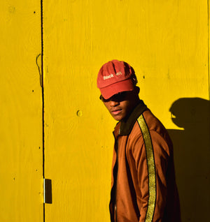 "Young Black man wearing a pink ""Black Joy"" hat against a yellow background.."