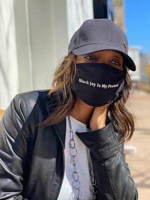 "A young Black woman is wearing a ""Black Joy Is My Protest"" mask."