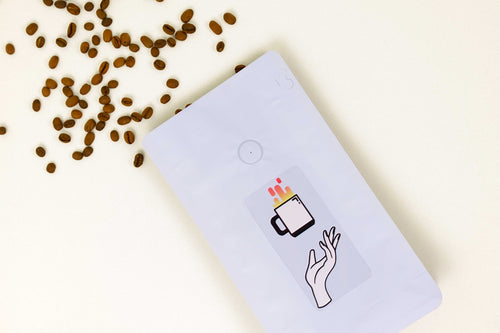 A bag of Peachy Keen coffee lying on a flat surface with beans coming out of the top.