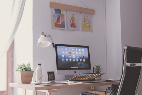 Creative workspace with colorful wall art and iMac computer on goldenlightstartup.com