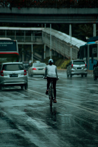 Woman cycling on wet city road
