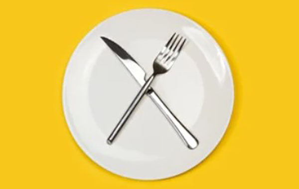 Fork and knife crossed on white plate with yellow background