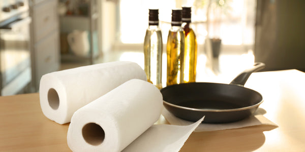 Paper towels siting next to frying pan and bottle of oil