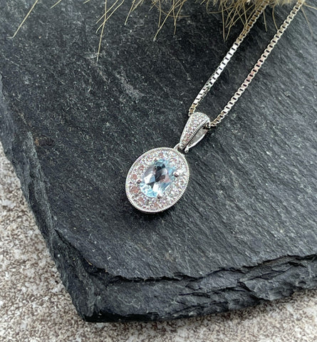 Oval aquamarine and diamond halo pendant