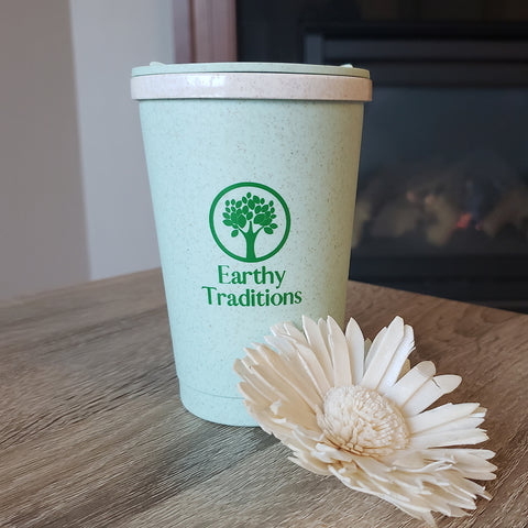 Earthy Traditions biodegradable cup on a table with a flower