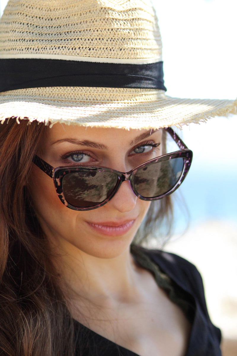 A photo of a beautiful woman wearing a hat and a pair of sunglasses.