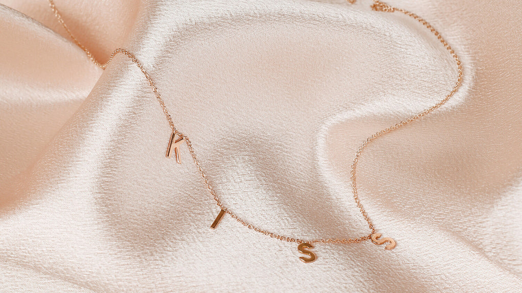 Kiss message necklace in 14k yellow gold for ModSet Jewelry about page
