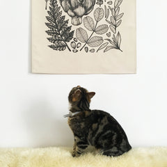 A small tabby cat looking up at a botanical wall hanging