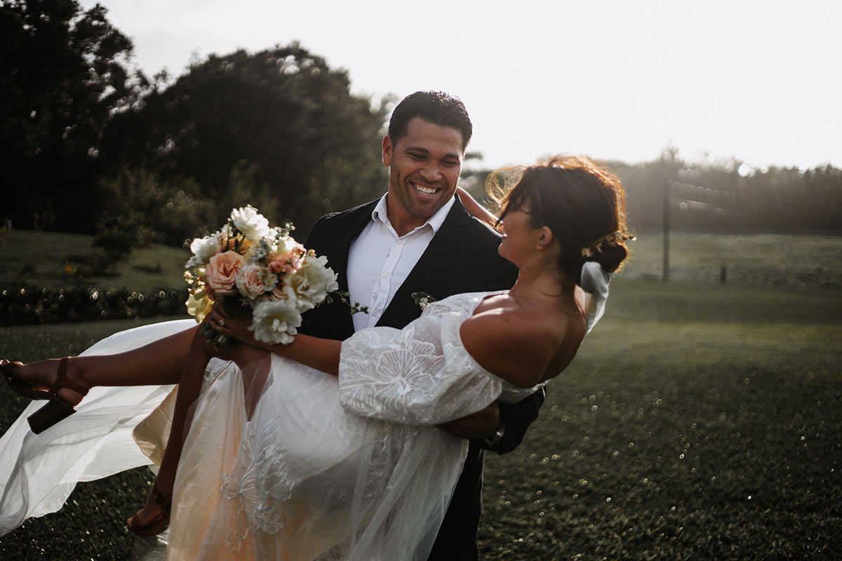 Groom carrying bride in a field by Theel Wedding Productions