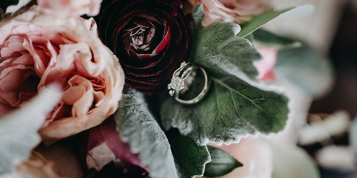 Wedding rings nestled in a pink and red bridal bouquet
