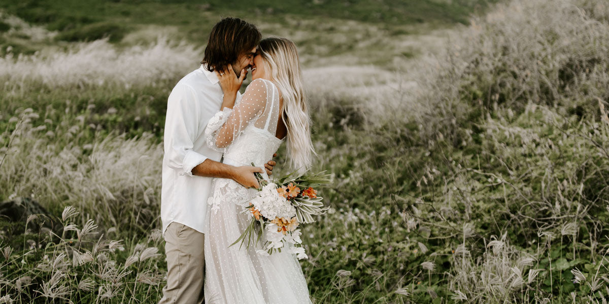A couple just married holding a bouquet and embracing in a field