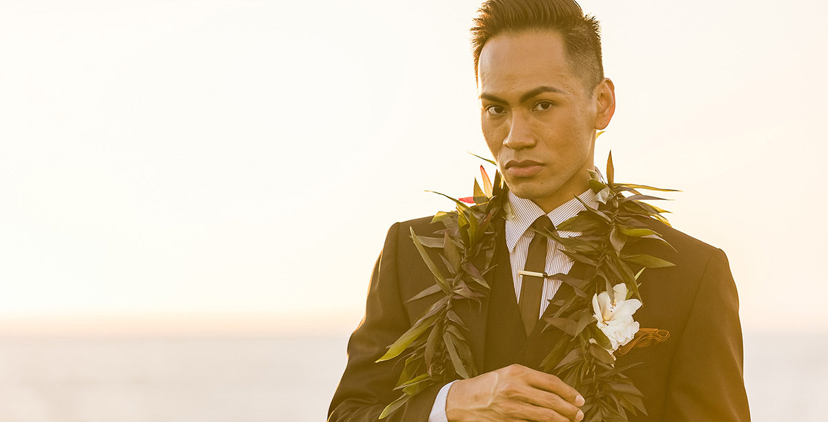 Close-up of a young man wearing a Maile ti-leaf lei and white orchid boutonniere