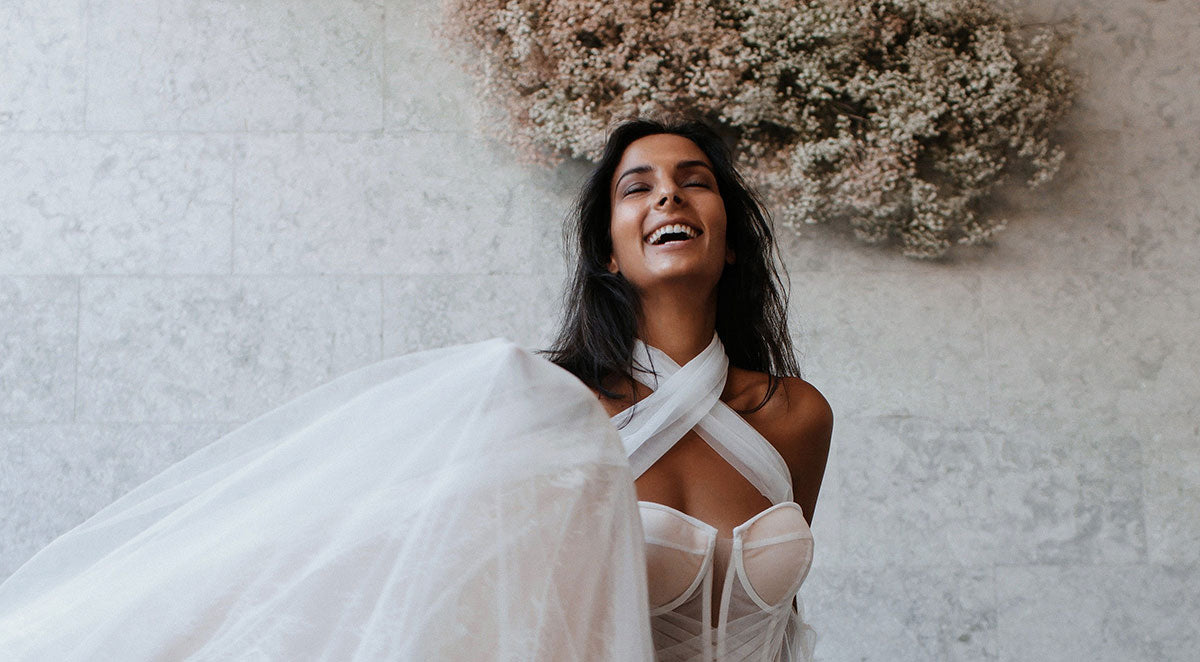 Closeup of bridal model wearing a bustier dress, laughing, with a flower cloud behind her