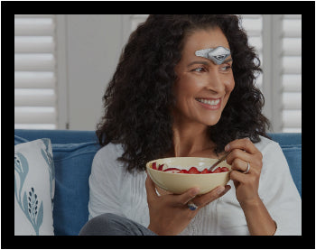 Woman eating on a couch while using her Cefaly device to prevent and treat her migraines