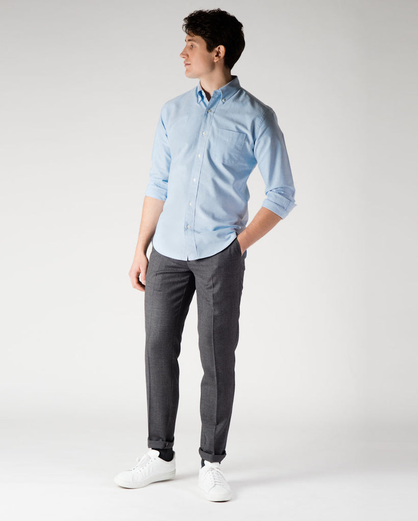 Blue oxford shirt with wool trousers and common projects sneakers.